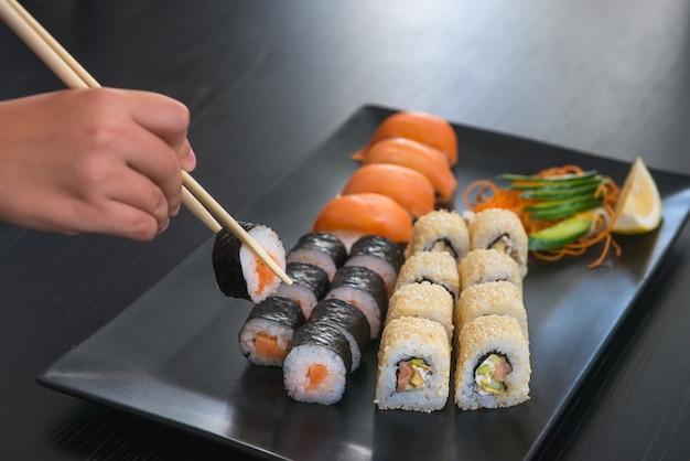 A mão do ser humano toma um rolo, um do grupo do sushi em uma placa retangular preta, com gengibre e os chopsticks conservados, fundo de madeira da tabela, foco seletivo. tema comida japonesa
