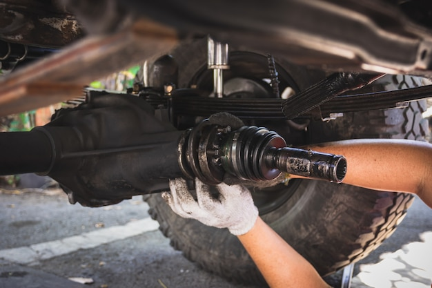 A mão do técnico está usando luvas de pano branco, consertando o eixo de propulsão do carro.