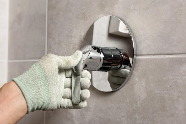 A mão do trabalhador é montada em uma torneira embutida