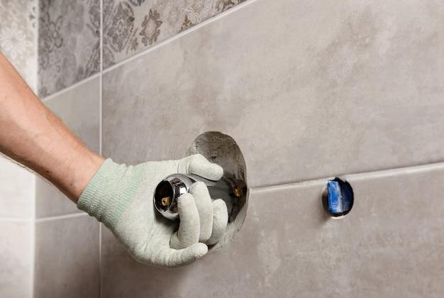 A mão do trabalhador está montando uma torneira embutida