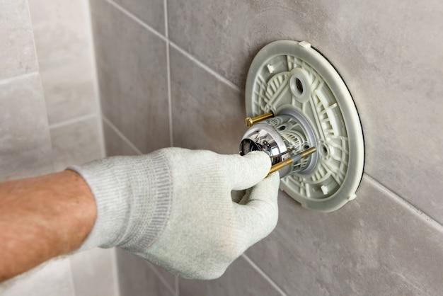 A mão do trabalhador está montando uma torneira embutida.