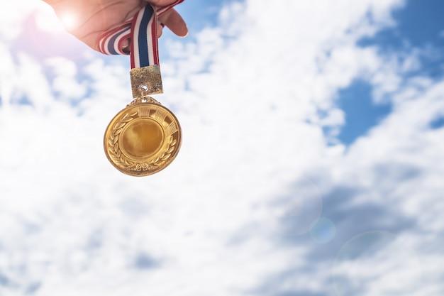 A mão do vencedor levantou medalhas de ouro guardando com a fita tailandesa contra o céu azul. medalha de ouro é prêmio