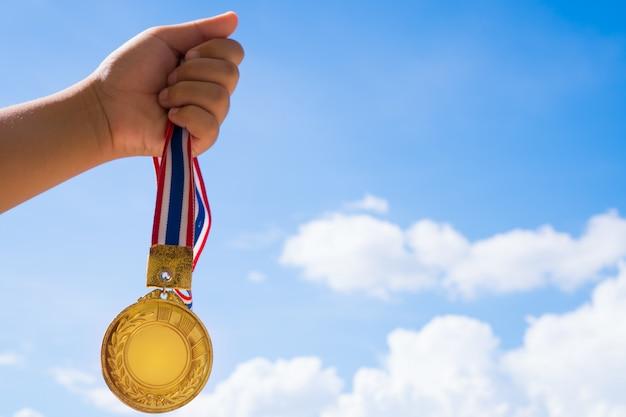A mão do vencedor levantou medalhas de ouro guardando com a fita tailandesa contra o céu azul.