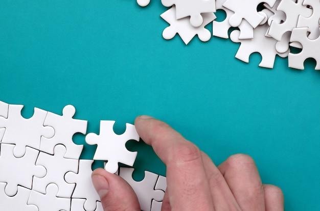 A mão dobra um quebra-cabeça branca e uma pilha de peças de quebra-cabeça desarrumada encontra-se