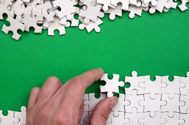 A mão dobra um quebra-cabeça branca e uma pilha de peças do quebra-cabeça descomposta