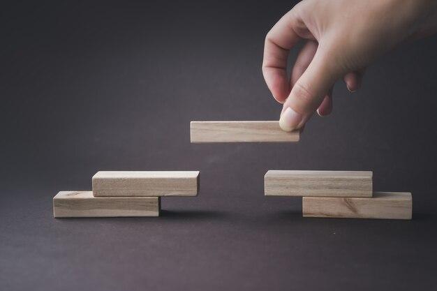 A mão dobra uma escada de blocos de madeira. sucesso, crescimento, vitória, vitória, desenvolvimento