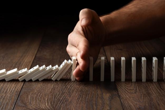 A mão dos homens parou efeito dominó, em uma madeira marrom