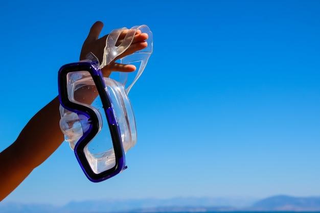 A mão dos miúdos está prendendo uma máscara para snorkeling na água e no céu azul. atividade familiar de verão