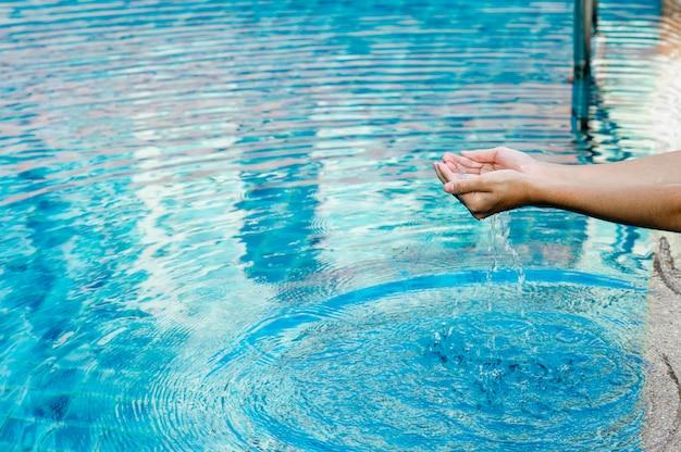 A mão e a água tocam a água azul. para atualizar o conceito de jogar água limpa com espaço da cópia.