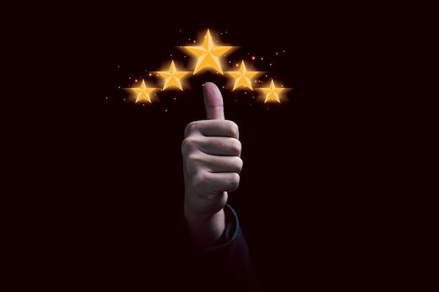 A mão e o polegar erguem-se com cinco estrelas douradas para a excelente classificação do cliente e avaliação do cliente sobre o conceito de serviço do produto.