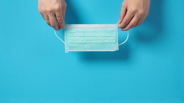 A mão é segurar máscara facial ou máscara cirúrgica sobre fundo azul.
