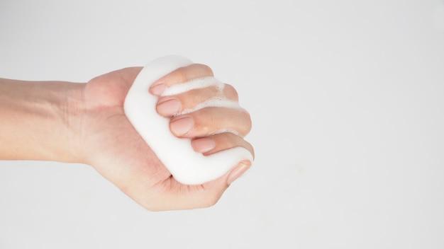 A mão é segurar o sabonete de espuma para as mãos para lavar no fundo branco.