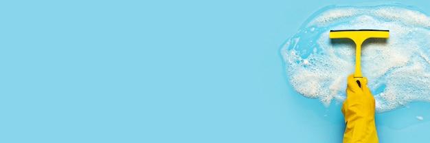A mão em uma luva de borracha amarela segura um raspador para limpar e limpa a espuma de sabão sobre uma superfície azul. conceito de limpeza, serviço de limpeza. . vista plana, vista superior