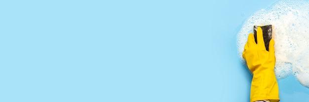 A mão em uma luva de borracha amarela segura uma esponja de limpeza e limpa uma espuma com sabão sobre uma superfície azul. conceito de limpeza, serviço de limpeza. . vista plana, vista superior