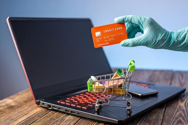 A mão em uma luva estéril segura um carrinho de compras com cartão de crédito. compra pela internet durante a pandemia de coronavírus