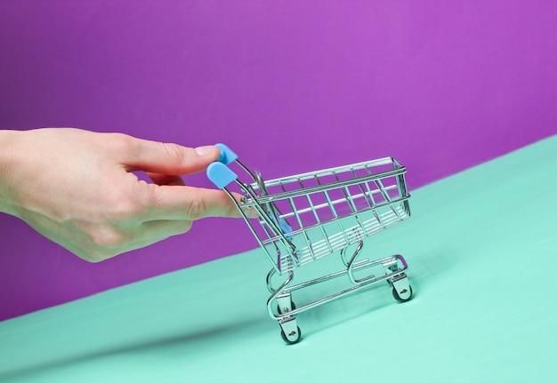 A mão empurra o mini carrinho de compras vazio inclinado