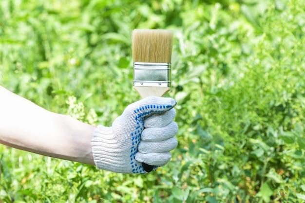 A mão enluvada de um homem segura uma escova larga para pintar em um verde.