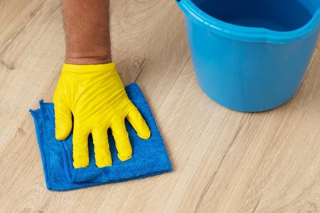 A mão enluvada lava um piso laminado com um pano úmido