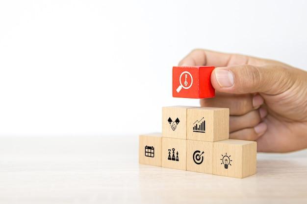 A mão escolhe a pilha de blocos de madeira do cubo com a tecla no ícone de estratégia de negócios