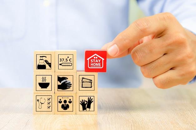 A mão escolhe o brinquedo de bloco de madeira da forma do cubo empilhado sem gráficos para o conceito de projeto de negócios e atividade para habilidades de prática de fundação de criança.