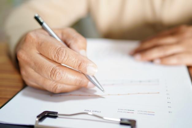 A mão escreve e trabalha na folha de papel na tabela no escritório.