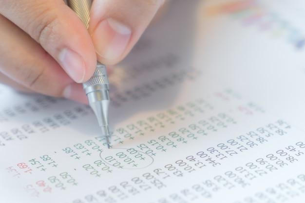 A mão escreve em várias cartas financeiras na tabela