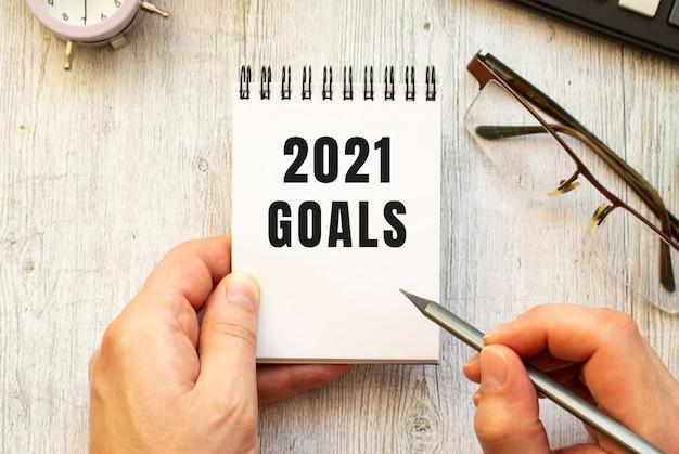 A mão escreve o texto objetivos 2021 a lápis em um caderno