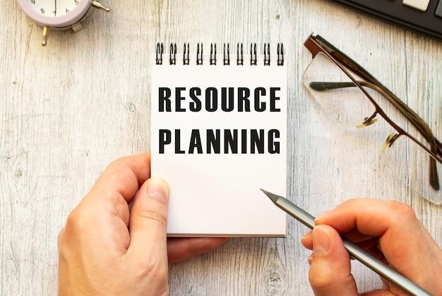 A mão escreve o texto planejamento de recursos a lápis em um caderno