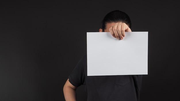 A mão esquerda do modelo masculino está segurando um papel a4 em branco sobre fundo preto.