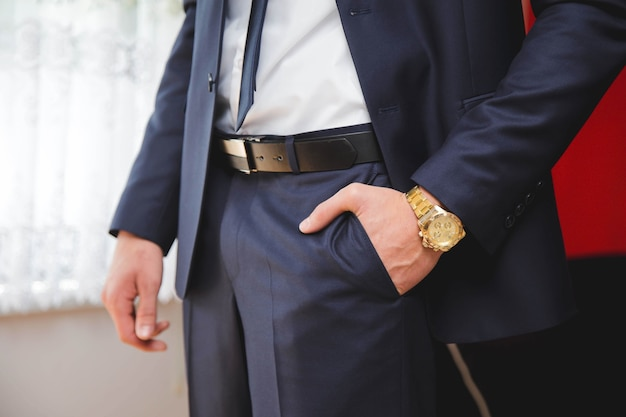 A mão esquerda do noivo no bolso