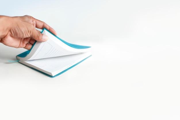 A mão esquerda está abrindo o caderno em um fundo branco