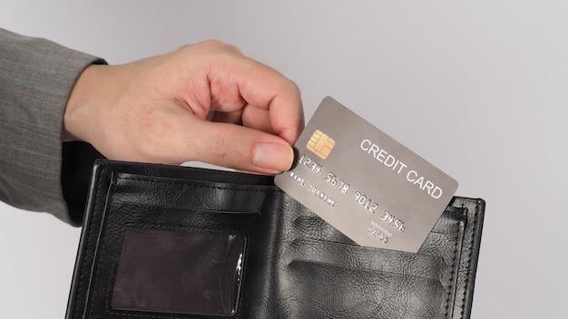 A mão esquerda usar terno cinza está segurando um cartão de crédito preto. cor preta na carteira em fundo branco.