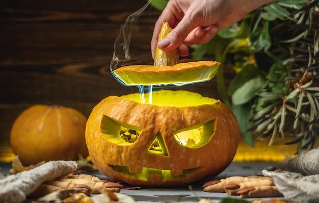 A mão está abrindo uma abóbora com um rosto recortado para o halloween