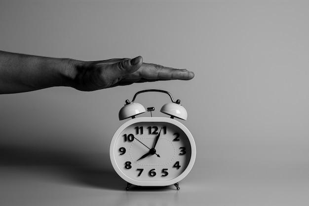 A mão está batendo para destruir e parar um despertador.