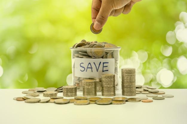 A mão está colocando moedas na garrafa e acumulando na coluna que representa economia de dinheiro ou ideia de planejamento financeiro para a economia.