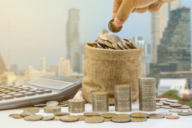A mão está colocando moedas no saco e acumulando na coluna que representam economia de dinheiro ou ideia de planejamento financeiro para a economia.