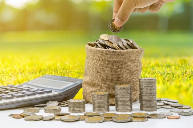 A mão está colocando moedas no saco e as moedas se acumulam na coluna que representam economia de dinheiro ou ideia de planejamento financeiro para a economia.
