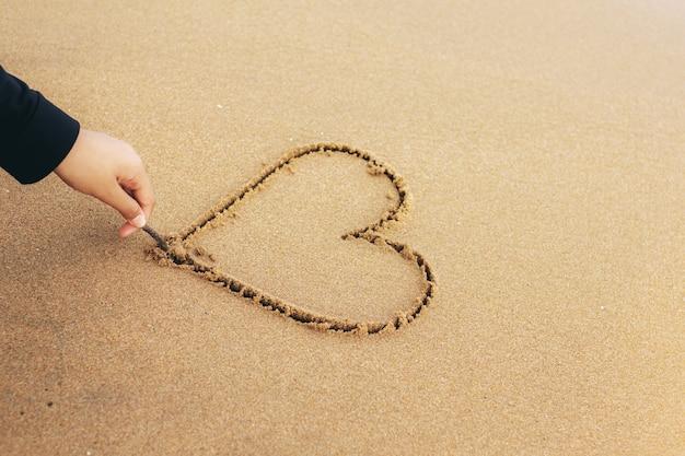 A mão está desenhando um coração na areia.