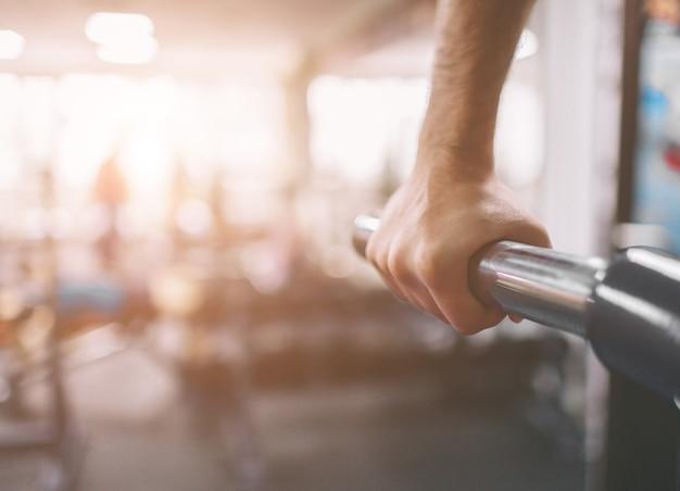 A mão está em close. treino no ginásio. mergulha em barras paralelas. fitness indoor.