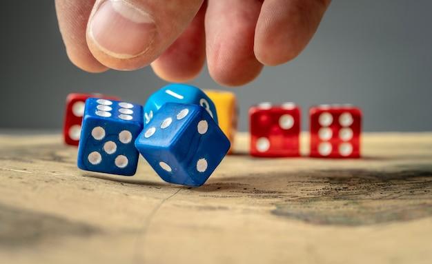 A mão está jogando os dados azuis no mapa. o conceito de jogos de tabuleiro e uma chance de sorte de ganhar