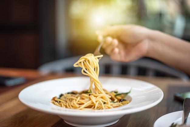 A mão está pegando o espaguete com um garfo