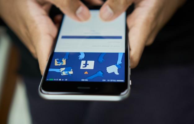 A mão está pressionando a tela do facebook