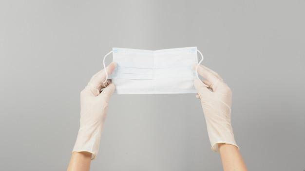 A mão está segurando a máscara cirúrgica. máscara médica em fundo cinza.