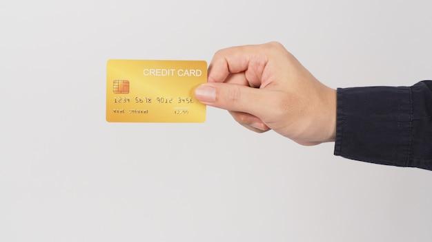A mão está segurando o cartão de crédito ouro isolado no fundo branco. mão do homem asiático.
