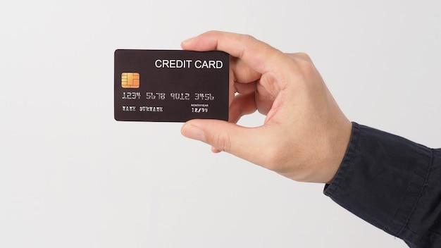 A mão está segurando o cartão de crédito preto, isolado no fundo branco. mão do homem asiático.