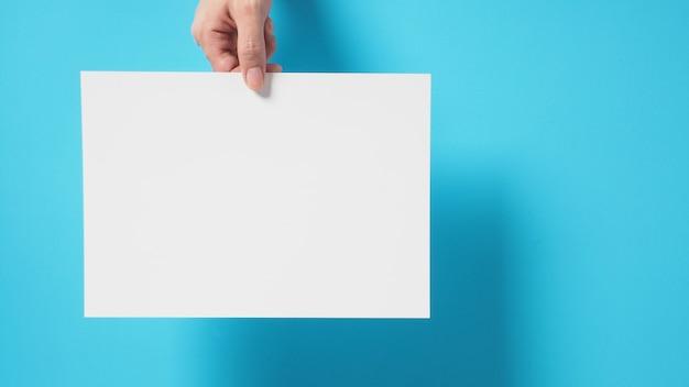 A mão está segurando o papel a4 em fundo azul.
