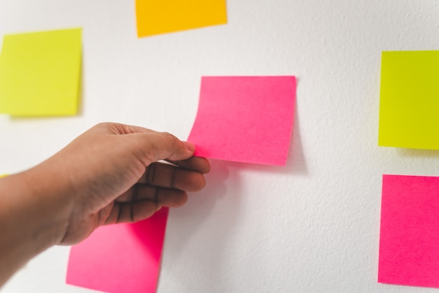 A mão está segurando o post-it preso à parede. brainstorming de conceito, compartilhar a ideia.