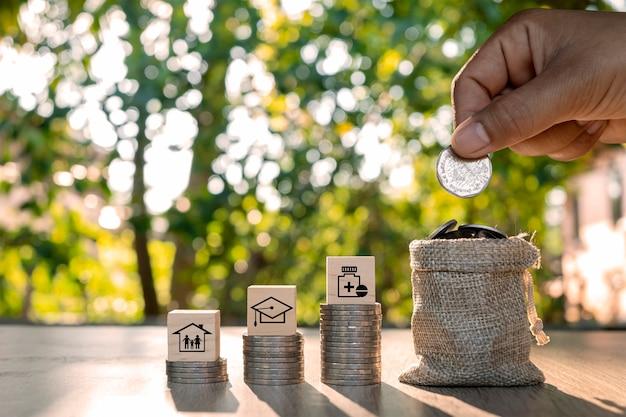 A mão está segurando uma moeda em uma sacola para economizar dinheiro e ícones de família, educação e saúde na pilha de madeira e dinheiro.