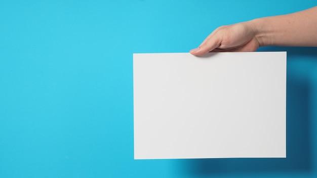 A mão está segurando uma placa a4 vazia em branco ou papel com fundo azul