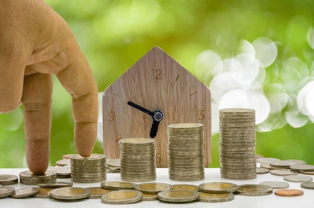 A mão está tocando moedas e moedas se acumulam em coluna que representam economia de dinheiro ou ideia de planejamento financeiro para a economia.